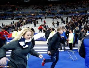 Spectators invade the pitch of the Stade de France stadium after the international friendly soccer match between France and Germany in Saint Denis, outside Paris, Friday, Nov. 13, 2015. Hundreds of people spilled onto the field of the Stade de France stadium after explosions were heard nearby during a friendly match between the French and German national soccer teams. French President Francois Hollande says he is closing the country's borders and declaring a state of emergency after several dozen people were killed in a series of unprecedented terrorist attacks.  (AP Photo/Christophe Ena)